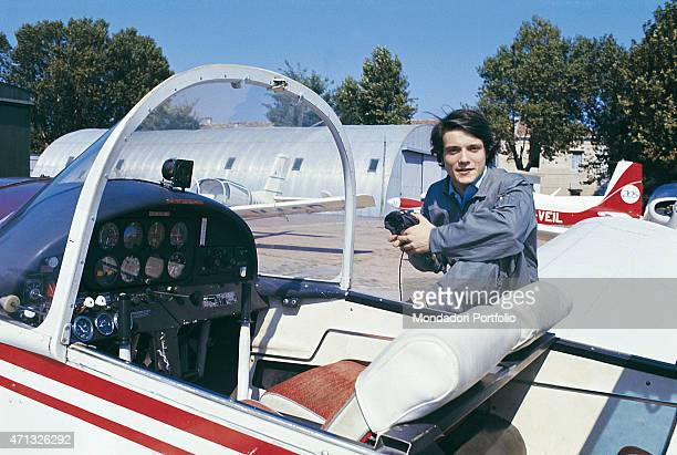 Italian singer and theatre actor Massimo Ranieri posing resting his leg against an airplane for a photo shooting in a small airport Italy 1971