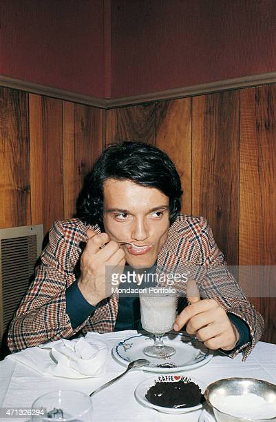 Italian singer and theatre actor Massimo Ranieri sitting in a caf and eating an icecream Photo shooting Italy 1973