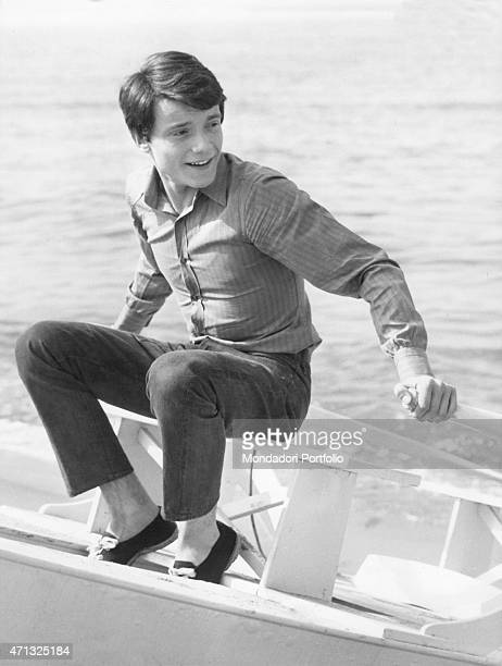 Italian singer and theatre actor Massimo Ranieri sitting on the rescue twinhull pleasure boat in a photo shooting at the sea Italy 1968