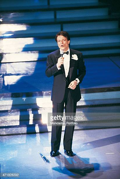 Italian singer and theatre actor Massimo Ranieri standing in dinner jacket on stage at the 38th Sanremo Music Festival won by him with the song...