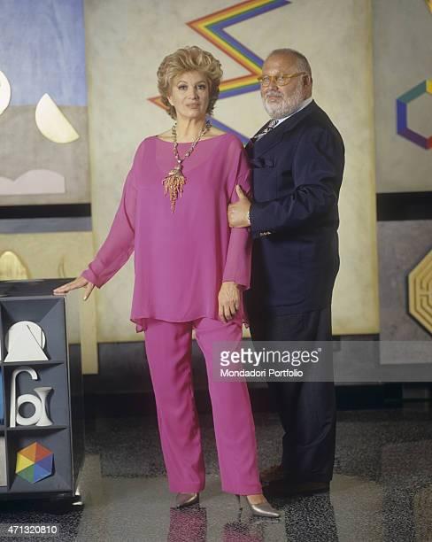 Italian singer and TV presenter Iva Zanicchi in a pink suit posing beside Italian fashion designer Gianfranco Ferr at his atelier on via Pontaccio...