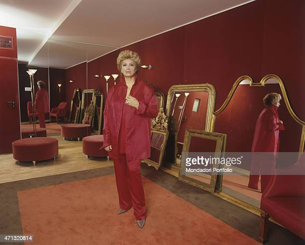 Italian singer and TV presenter Iva Zanicchi in a red suit posing beside many mirrors resting against the wall at Italian fashion designer Gianfranco...