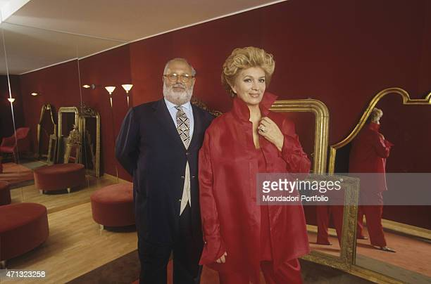 Italian singer and TV presenter Iva Zanicchi in a red suit smiling beside Italian fashion designer Gianfranco Ferr at his atelier on via Pontaccio...