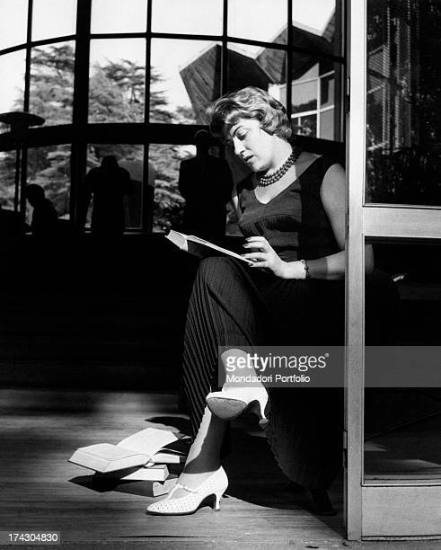 Italian singer Carla Boni reading a book inside the public library in Parco Sempione designed by Ico Parisi and Silvio Longhi with some decorations...