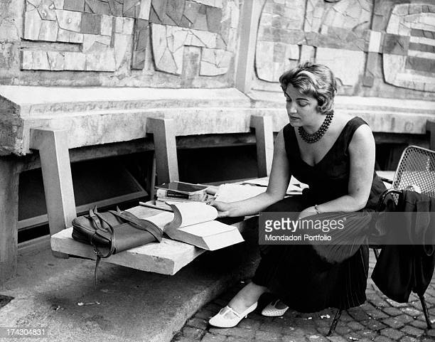 Italian singer Carla Boni sitting on a bench decorated by Bruno Munari Francesco Somaini and Bruno Reggiani placed outside the public library in...