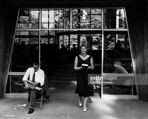 Italian singer Carla Boni standing outside the public library in Parco Sempione designed by Ico Parisi and Silvio Longhi with some decorations by...