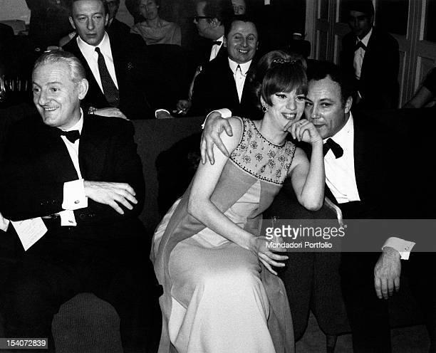 Italian singer Claudio Villa hugging Italian singer and TV presenter Iva Zanicchi Sitting with them Italian journalist Ugo Zatterin Sanremo 1967