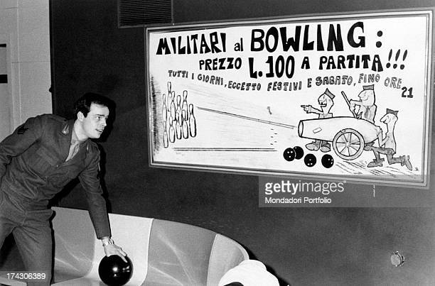 Italian singer Dino holding a bowling ball and looking at the sign with the soldiers' fare for a match Turin 1970s