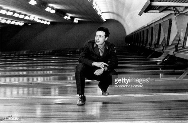 Italian singer Dino wearing a military uniform and crouching on a bowling alley Turin 1970s