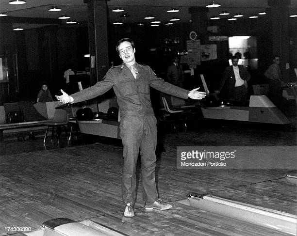 Italian singer Dino wearing the military unifrom and smiling with his arms open on a bowling alley Turin 1970s
