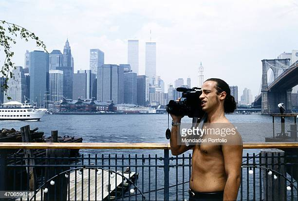 'Italian singer Eros Ramazzotti makes a shot with a shoulder camera on the bank of the East River near the Brooklyn Bridge with New York skyline on...