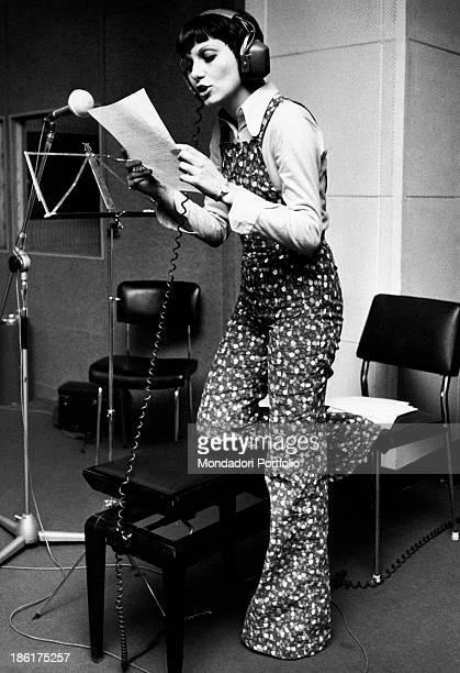 Italian singer Gilda Giuliani rehearsing a song in a recording studio Milan 1970s