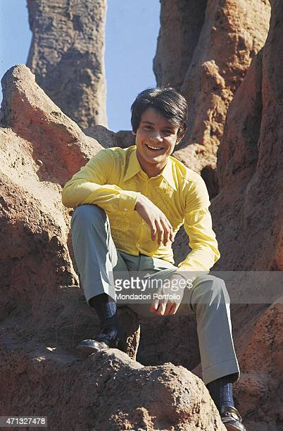 Italian singer Massimo Ranieri posing smiling among some artificial rocks in a photo shooting at the fun fair Italy 1968