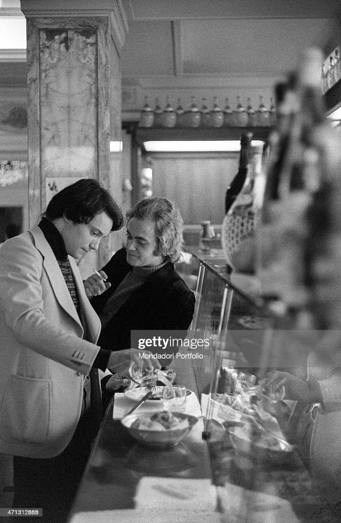 Italian singer Massimo Ranieri pouring a glass for himself in the cafeteria next to his place Rome 1970
