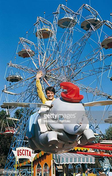 Italian singer Massimo Ranieri riding a Dumbo shaped switchback in a photo shooting at the fun fair Italy 1968