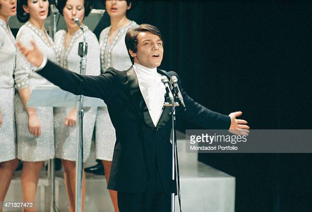 Italian singer Massimo Ranieri standing on the stage at the 19th Sanremo Music Festival where he sings the song 'Quando l'amore diventa poesia' with...