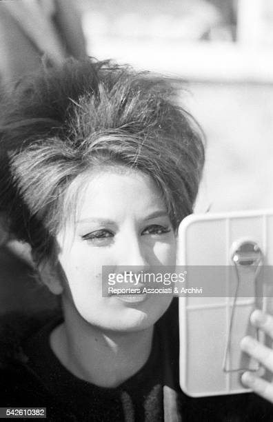 Italian singer Mina looking at herself in a mirror on the set of Mina fuori la guardia Rome 14th February 1961