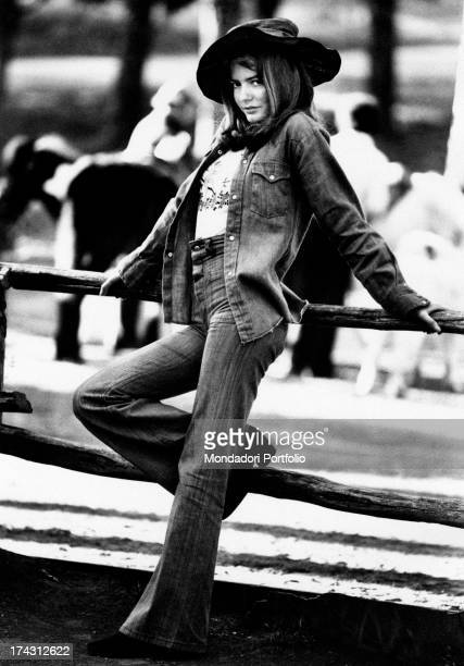 Italian singer Nada posing leaning against a fence and wearing in bellbottoms jeans and a hat on her head Rome 1970s