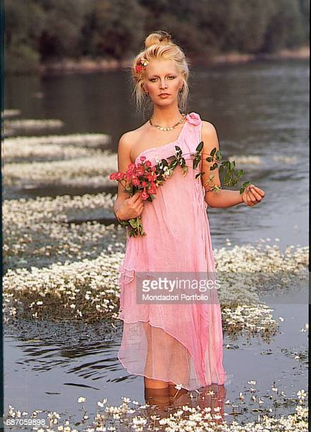 Italian singer Patty Pravo holding some flowers in a river Italy 1980s