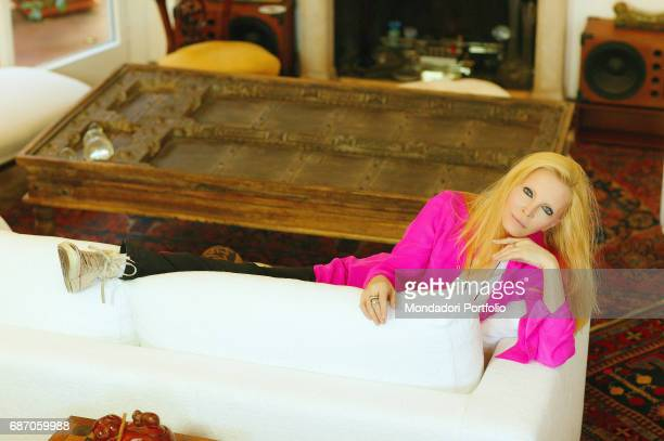 Italian singer Patty Pravo leaning on a sofa in her house in Rome Rome 1990s