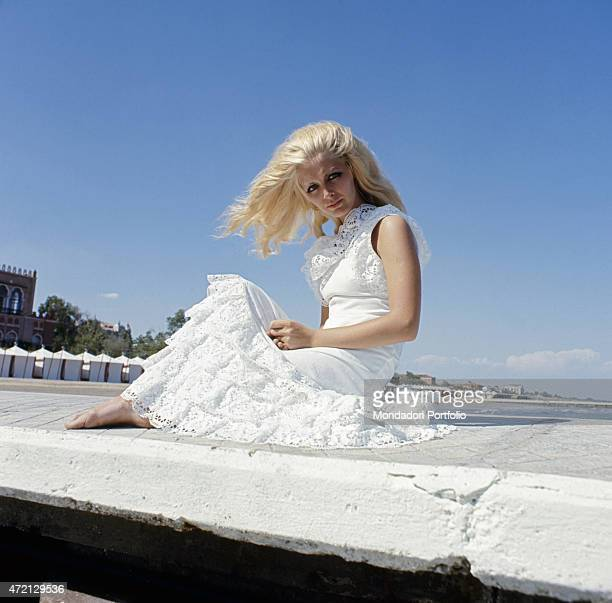 Italian singer Patty Pravo on the seafront wearing a white dress 1970s
