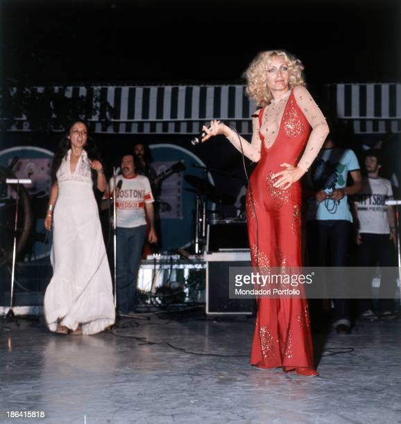 Italian singer Patty Pravo performing during a concert in a red low neck closefitting jumpsuit 1974