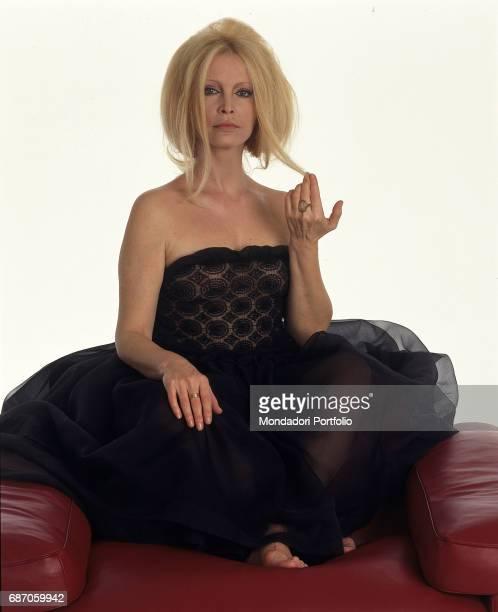 Italian singer Patty Pravo sitting on an armchair in an elegant seethrough black dress Italy 1990s