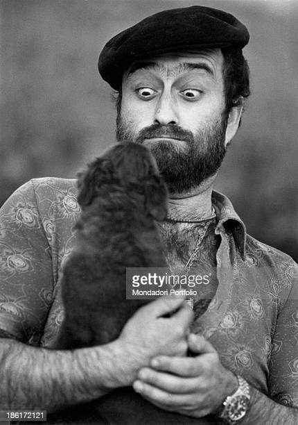 Italian singer songwriter and musician Lucio Dalla grimacing at the dog that he's holding Sorrento 1970s