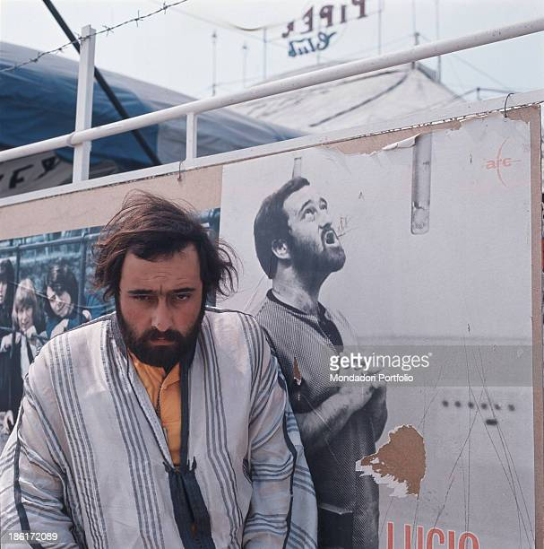 Italian singer songwriter and musician Lucio Dalla posing beside a poster of himself hanging outside the Piper Disco Club Rome 1967