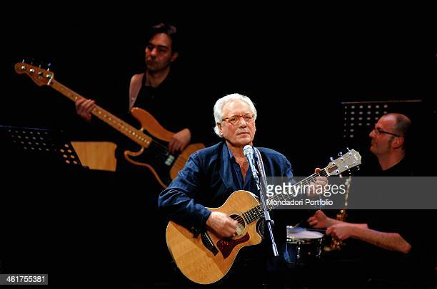 Italian singersongwriter actor and standup comedian Enzo Jannacci plays the guitar onstage the Condominio Theatre in Gallarate during the show The...