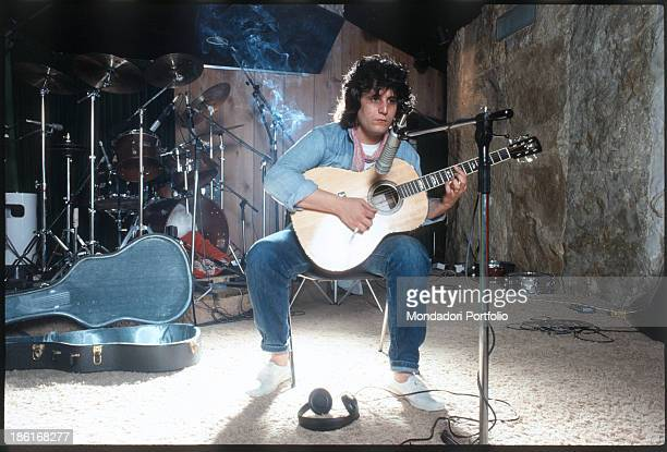 Italian singersongwriter and musician Pino Daniele performing on the stage singing and playing the classic guitar 1982