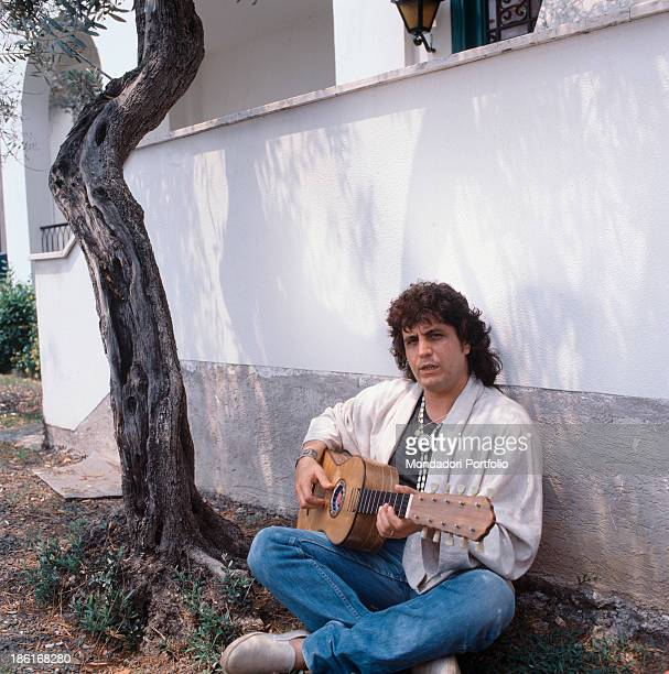 Italian singersongwriter and musician Pino Daniele playing guitar leaned against a wall 1987
