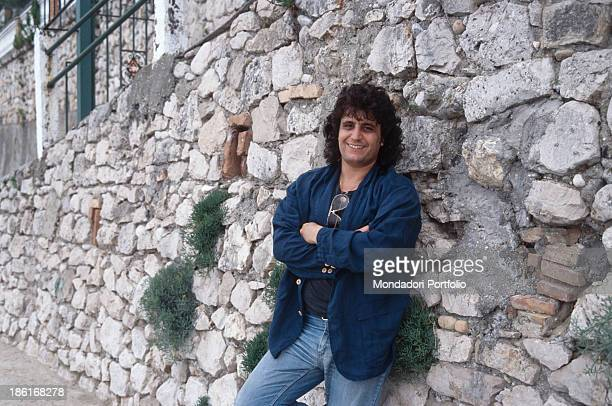 Italian singersongwriter and musician Pino Daniele smiling leaned against a stone wall 1987