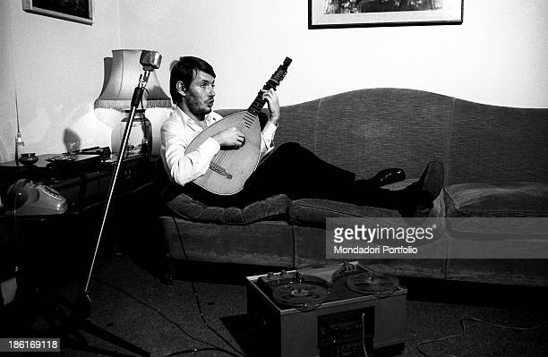 Italian singersongwriter Fabrizio De André singing and playing the lute lying on a sofa Genoa December 1969