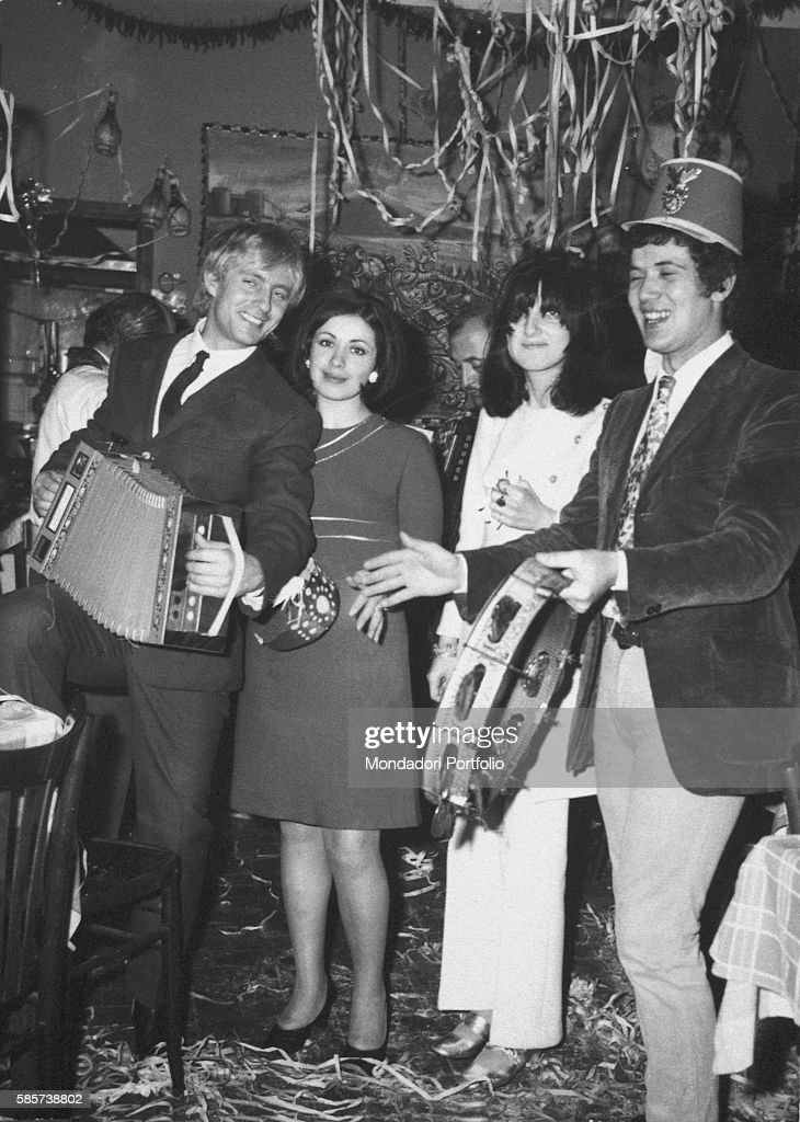 Italian singersongwriter Lucio Battisti playing the tambourine during a party beside his wife Velezia his sister Albarita and his brotherinlaw 1970s