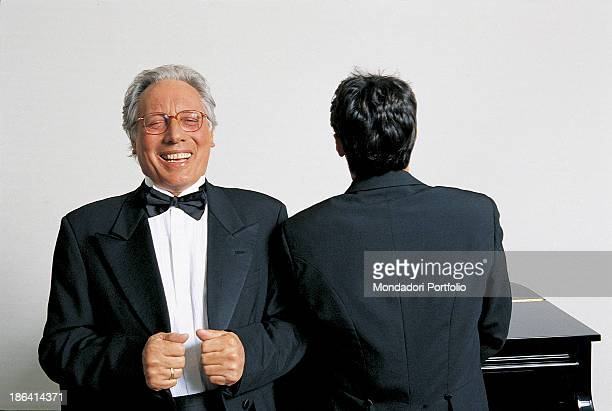 Italian singersongwriter standup comedian and actor Enzo Jannacci in dinner jacket laughing seated at the piano beside another man 1990s