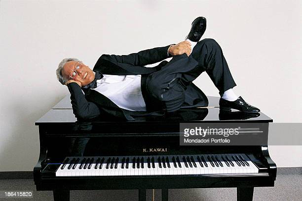 Italian singersongwriter standup comedian and actor Enzo Jannacci in dinner jacket resting his head on the head while lying on a piano 1990s