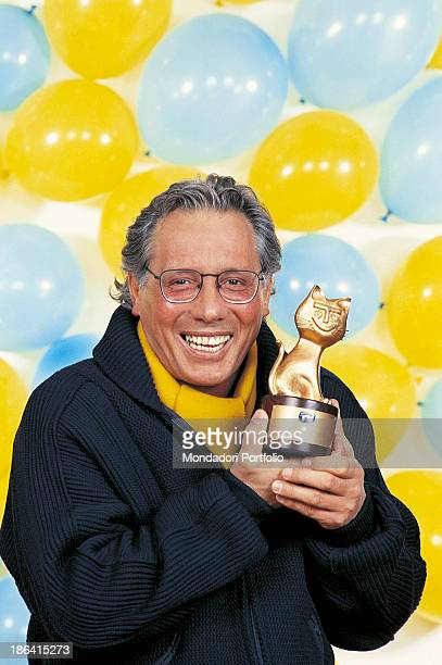 Italian singersongwriter standup comedian and actor Enzo Jannacci smiling holding the Telegatto award that he got for the 2nd Telegatto Television...