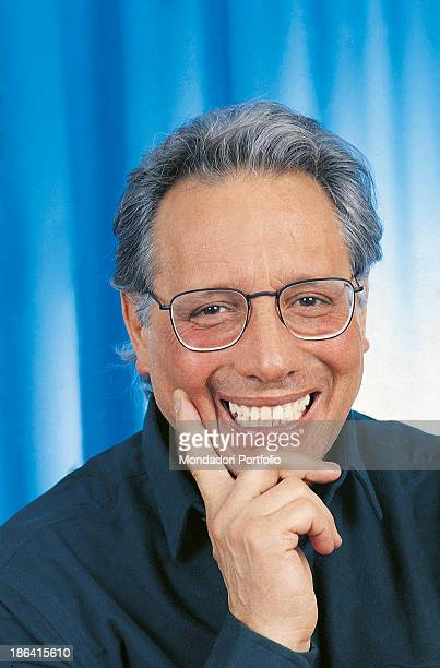 Italian singersongwriter standup comedian and actor Enzo Jannacci smiling with his hand under his chin 1980s