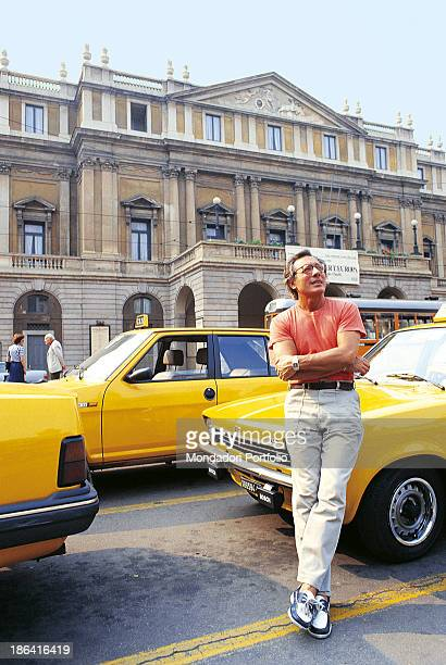 Italian singersongwriter standup comedian and actor Enzo Jannacci with folded arms leaning on a taxi in piazza della Scala Milan 1985