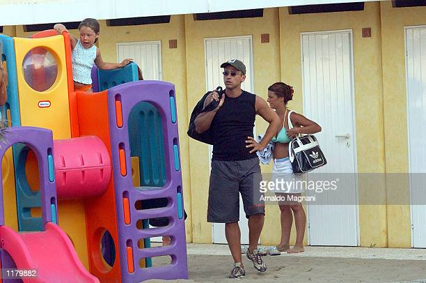 Italian soccer star Eros Ramazzotti plays with his daughter Aurora July 28 2002 at the Rouge Beach in Maritima Presso Milan Italy The woman at is...