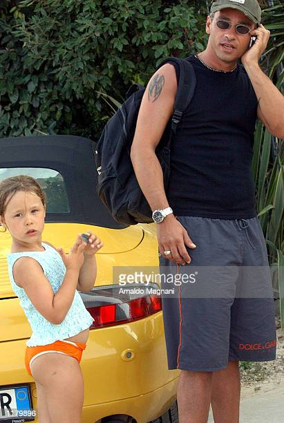 Italian soccer star Eros Ramazzotti talks an a cell phone with his daughter Aurora at his side July 28 2002 at the Rouge Beach in Maritima Presso...
