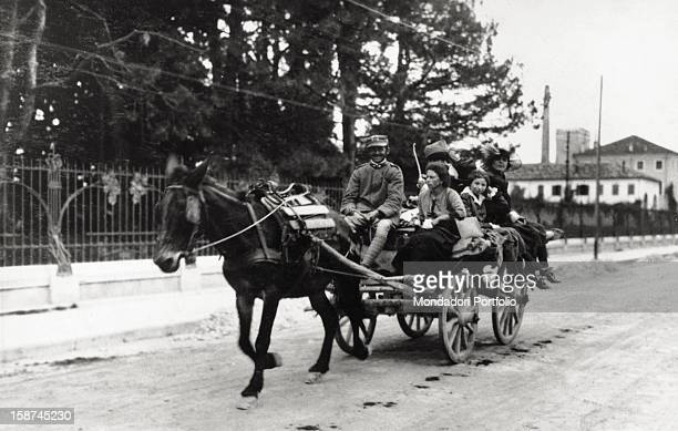 Italian soldier carrying some women on a horsedrawn cart after the end of World War I Vittorio Veneto 1918
