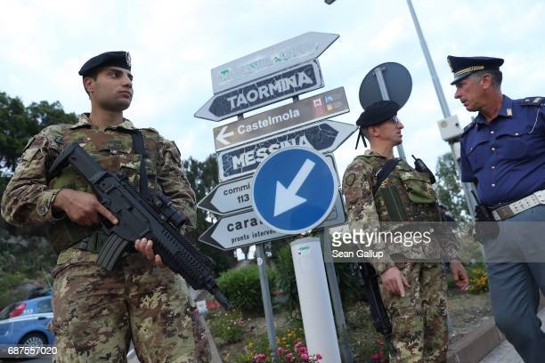 Italian soldiers and police stand at a checkpoint at a road leading up to the historic town of Taormina which will host the upcoming G7 summit on the...