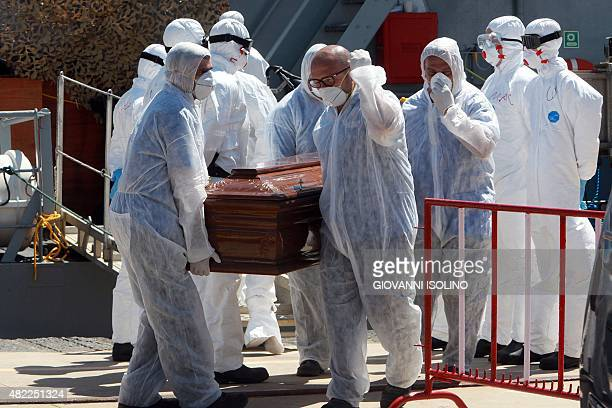 Italian soldiers carry one of the 13 coffins of migrants who died attempting the perilous crossing of the Mediterranean Sea at Messina harbour on...