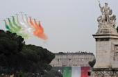 Italian special acrobatic unit airforce 'Frecce Tricolori' spread smoke with the colours of the Italian flag over Rome's ancient Coliseum during...