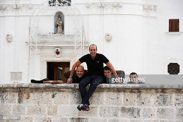 Italian standup comedian impersonator and musician Luca Medici best known with his stage name of Checco Zalone poses smiling sitting on a wall in...