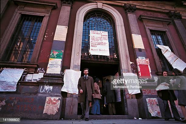 Italian student leaving the university Posters cover the walls of the university building in Via Festa del Perdono Milan 1974