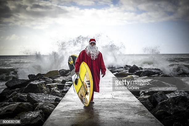 Italian SUP surfer Federico Piccinaglia dressed as Santa Claus poses with his board on December 1 2015 in Levanto near La Spezia AFP PHOTO / OLIVIER...