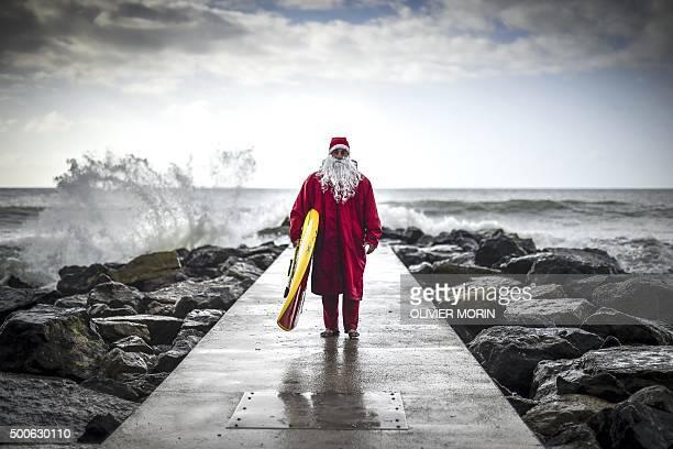 TOPSHOT Italian SUP surfer Federico Piccinaglia dressed as Santa Claus poses with his board on December 1 2015 in Levanto near La Spezia / AFP /...
